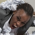 African business woman is tired of work . Sitting in front of crumpled paper pile . Unhappy with cv